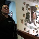Woman standing beside artwork on a wall