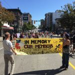 Two people carrying a yellow banner ahead of a large marching crowd in downtown Vancouver
