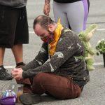 Man sitting cross legged on the sidewalk with his head down