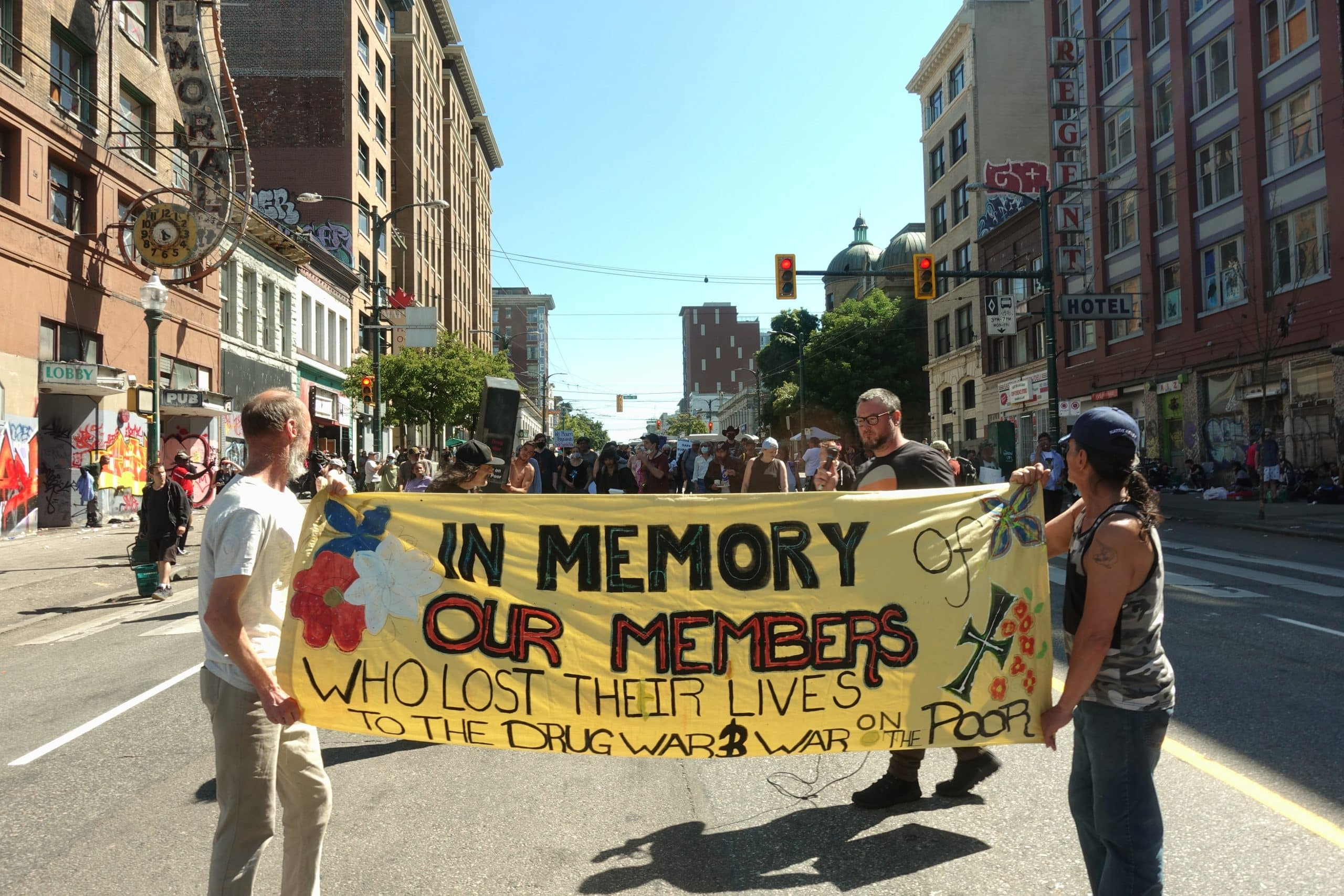 "Two people carry a large banner down the street that reads ""In Memory Our Members"""