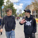 Dr. Mark Tyndall and Matt Bonn talking to each other while walking down a street
