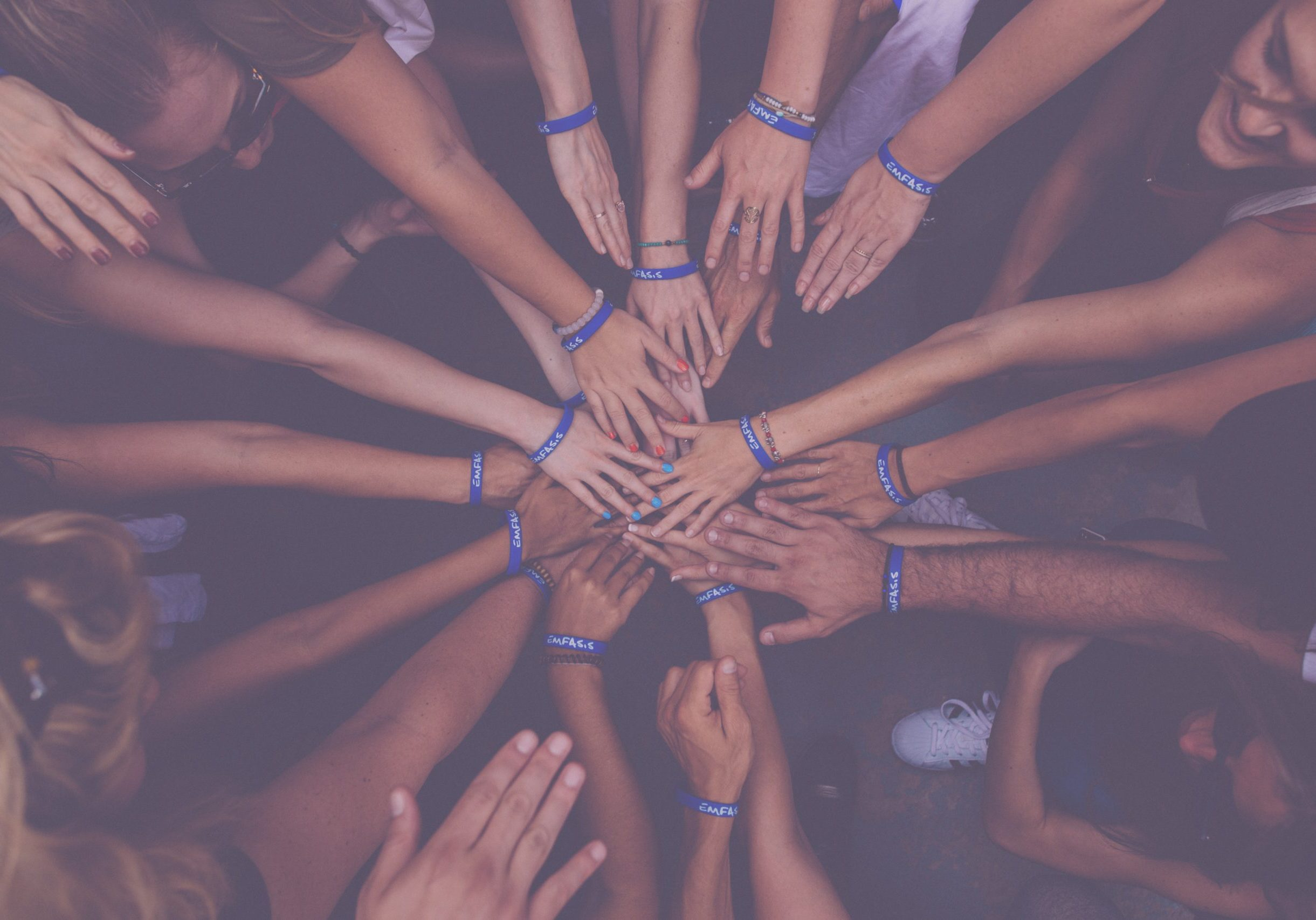 A circle of hands joining in the middle